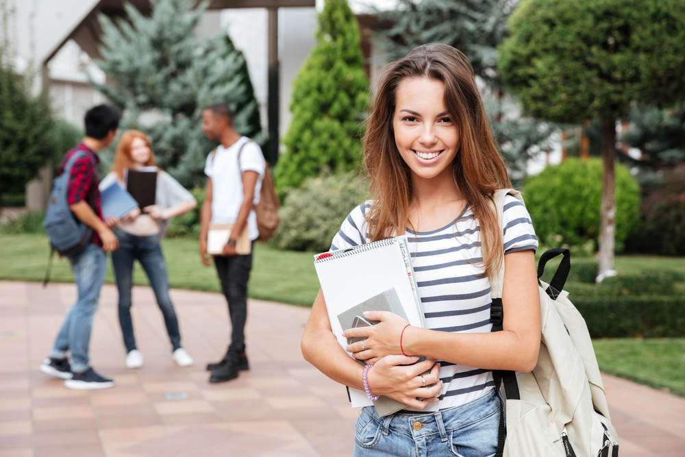 Cheerful beautiful young woman student with backpack standing in campus