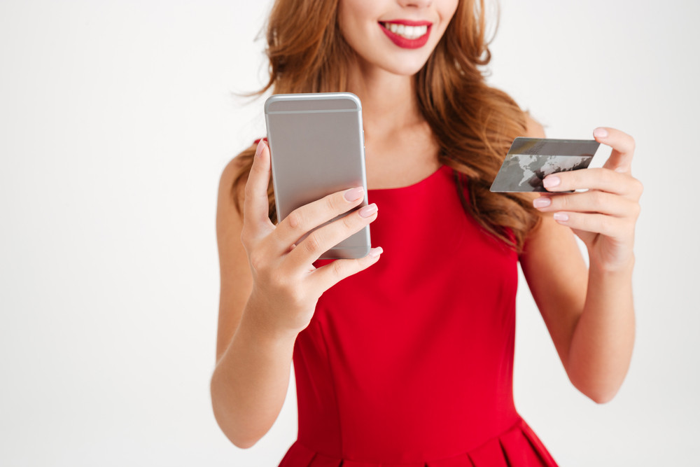Cheerful beautiful young woman using cell phone and credit card over white background