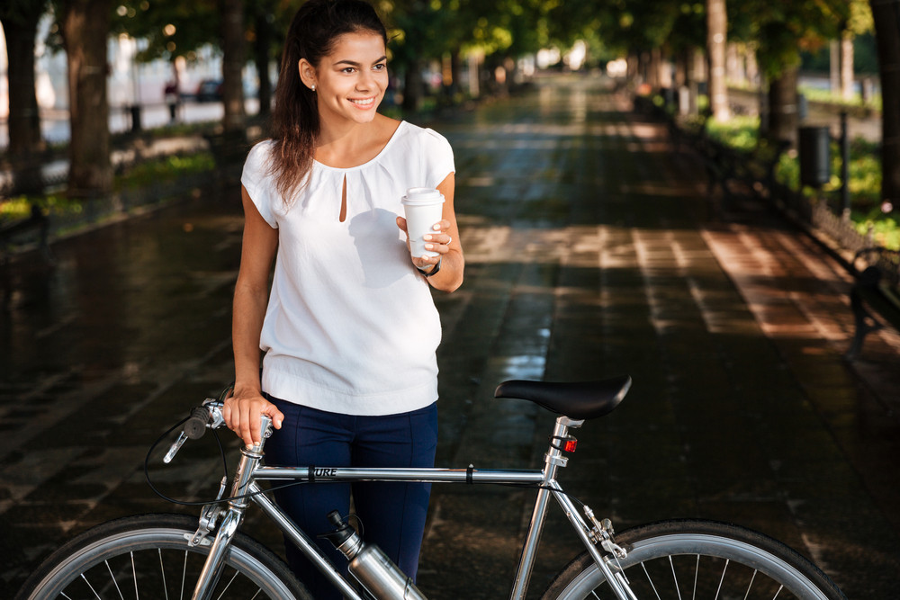 Cheerful brunette woman with takeaway coffee cup and bicycle in the park