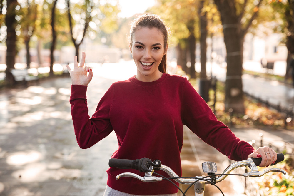 Cheerful caucasian lady dressed in sweater walking with her bicycle outdoors while making Ok gesture. Look at camera.