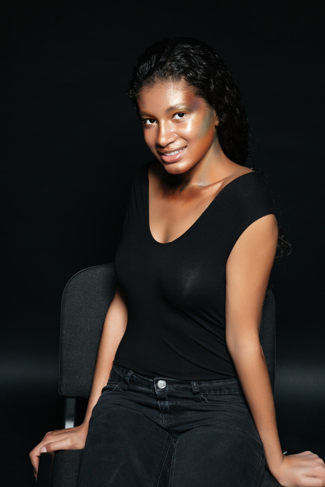 Cheerful charming african american young woman with fashion makeup sitting and posing on chair over black background