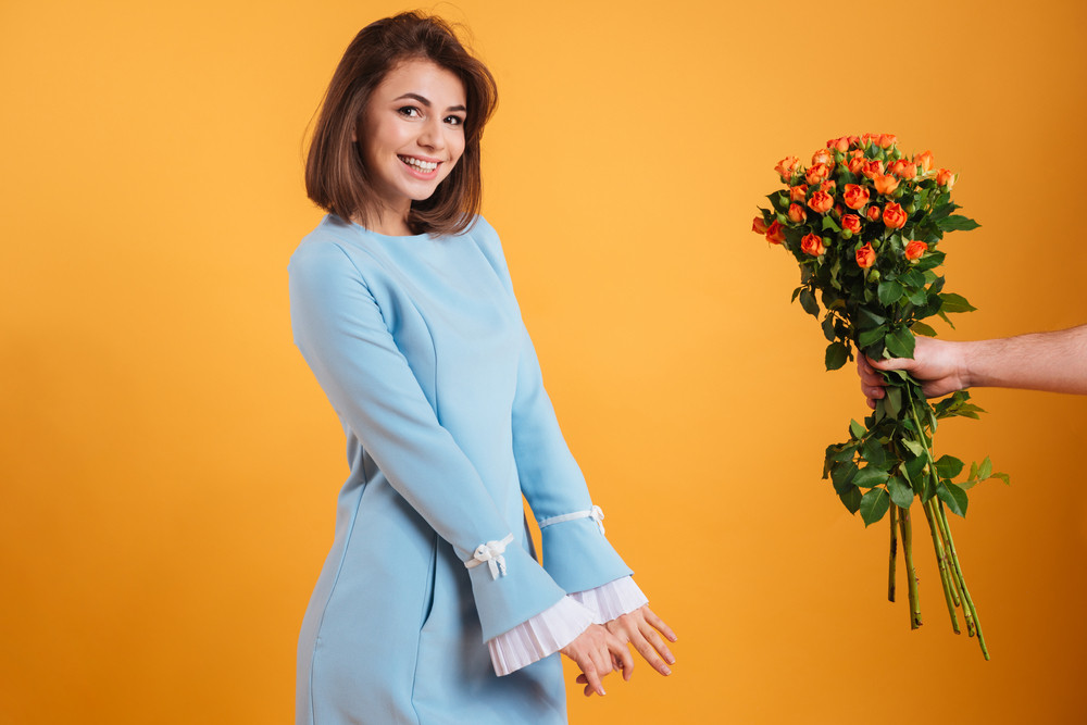 Cheerful charming young woman receiving bunch of flowers from her boyfriend over yellow background