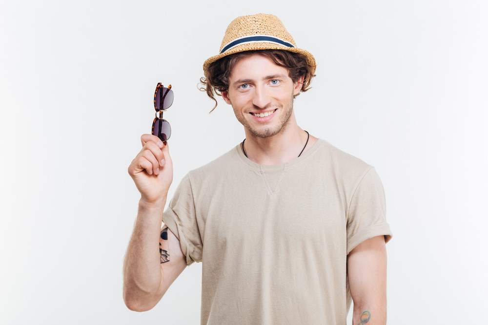 Cheerful confident young man in hat holding sunglasses over white background