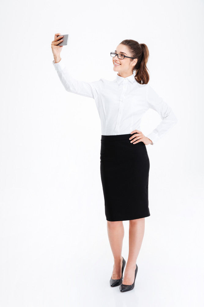 Cheerful cute young businesswoman in glasses standing and taking selfie using mobile phone over white background