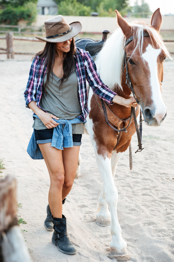 Cheerful cute young woman cowgirl walking with her horse in village