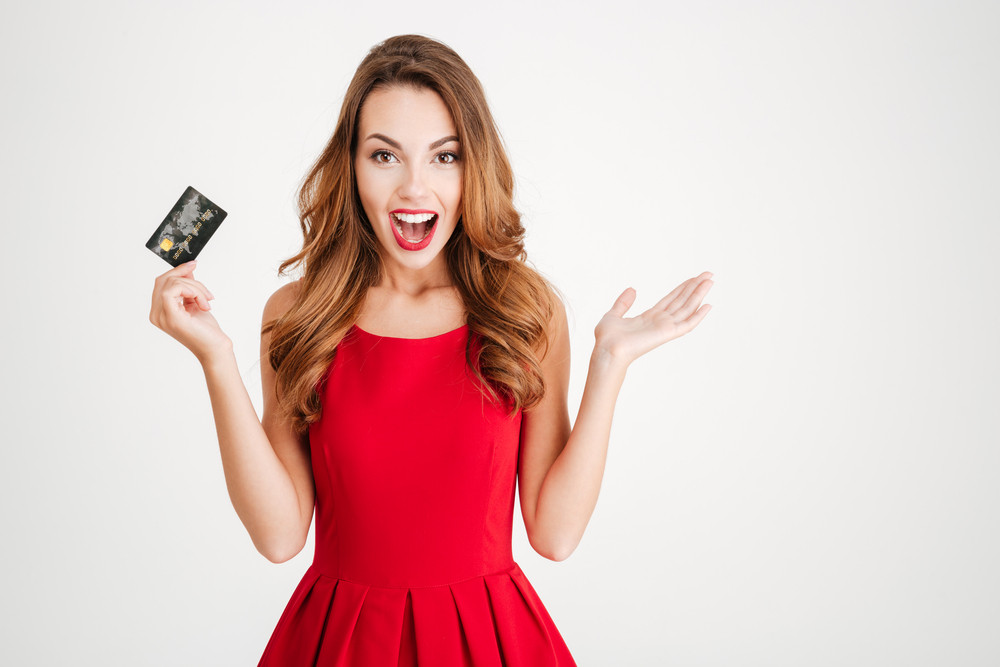 Cheerful excited surprised young woman with credit card over white background