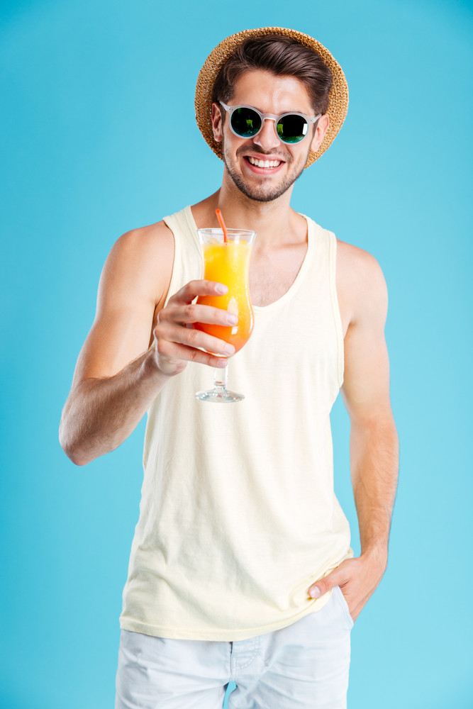 Cheerful handsome young man in hat and sunglasses holding glass of fresh juice over blue background