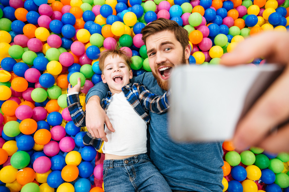 Cheerful joyful son and dad lying on colorful balls and taking selfie with smartphone