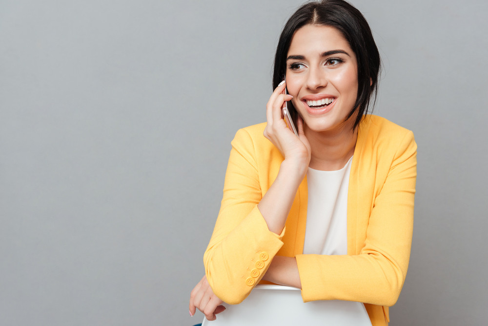 Cheerful lady dressed in yellow jacket sitting on stool over grey background while talking by her phone and looking aside.