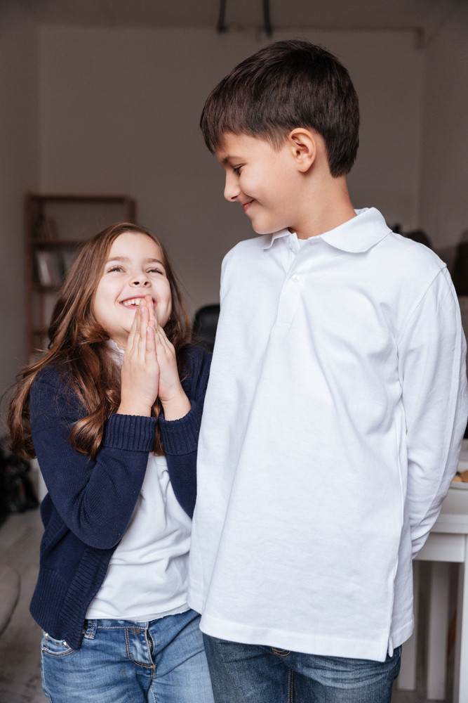 Cheerful little boy and girl talking and laughing together