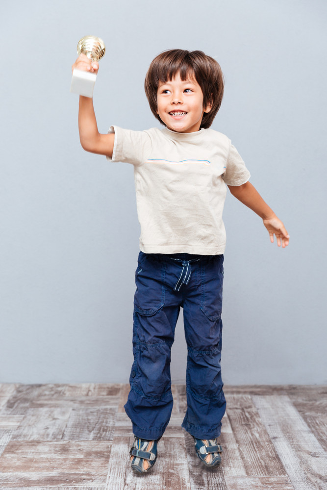 Cheerful little boy cup trophy jumping and laughing over gray background