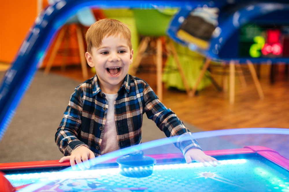 Cheerful little boy playing air hockey and having fun at indoor amusement park