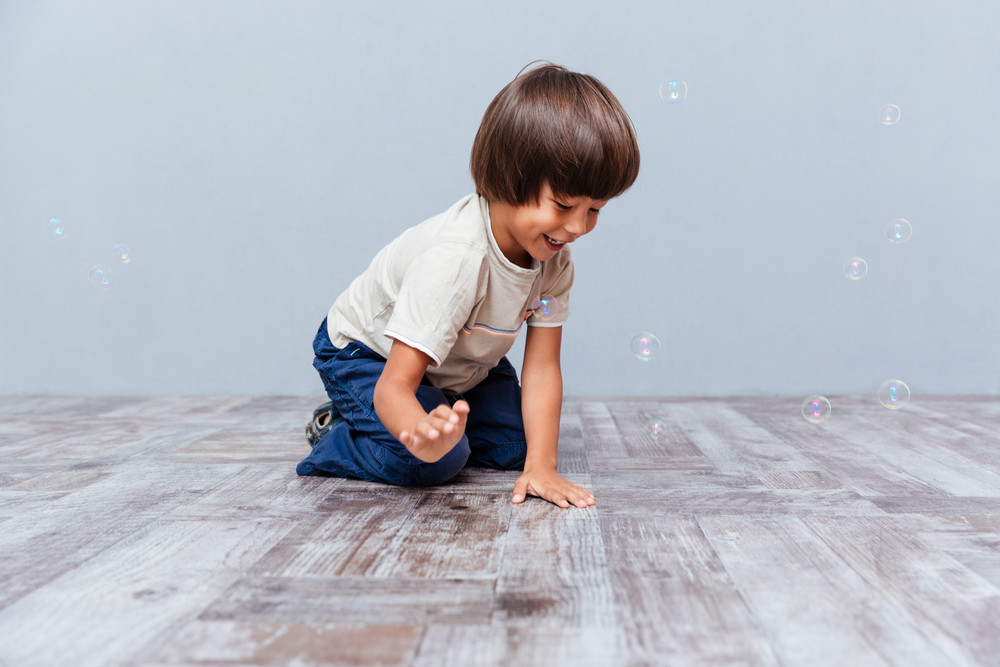 Cheerful little boy sitting and playing with soap bubbles over gray background