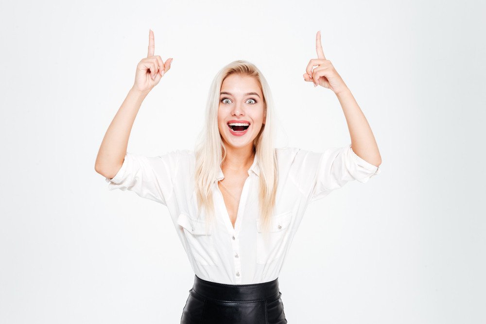 Cheerful lovely young businesswoman standing and pointing up over white background