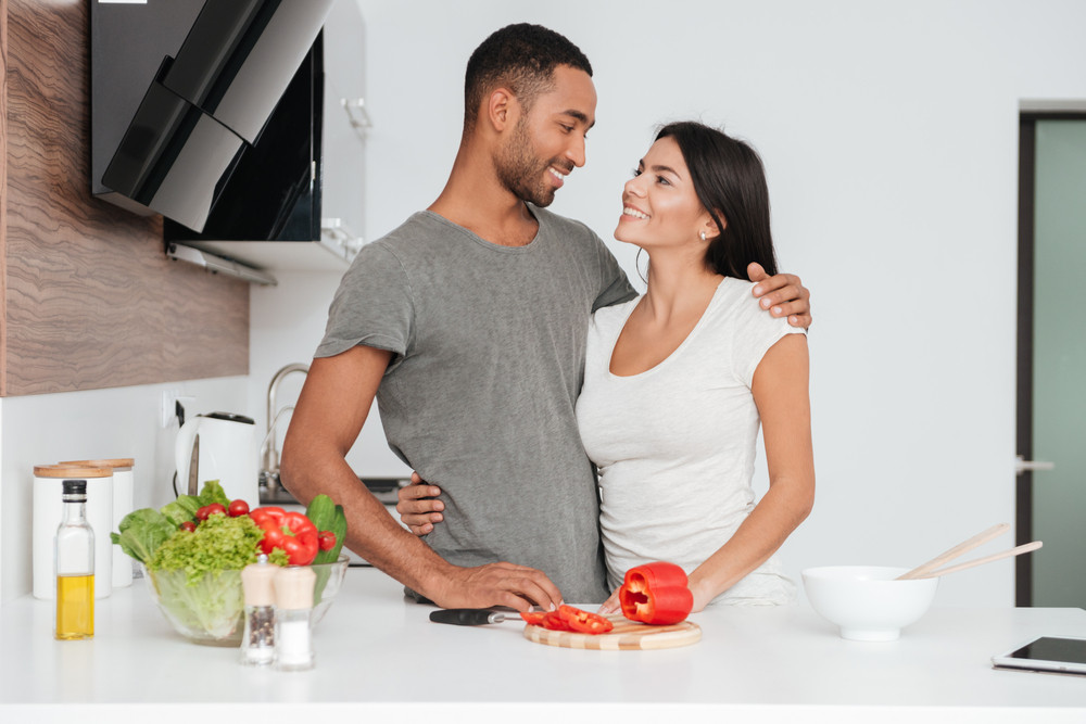 Cheerful loving couple in the kitchen hugging while cooking. Look at each other.