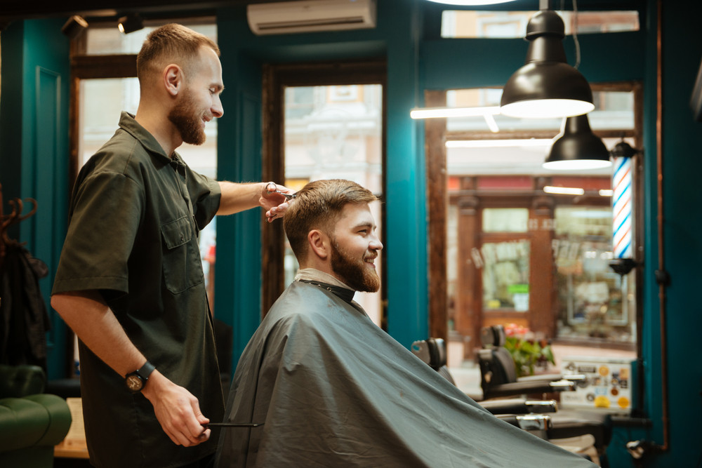 Cheerful man getting haircut by hairdresser with scissors while sitting in chair. Look aside.