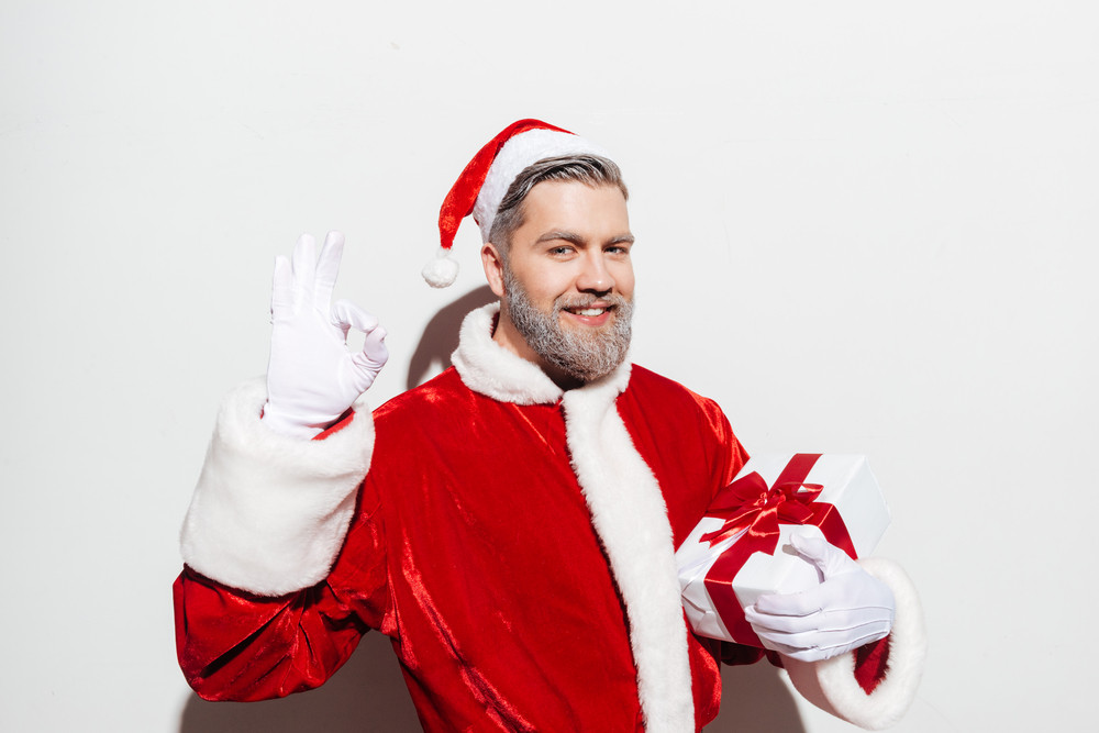 Cheerful man santa claus holding gift box and showing ok sign