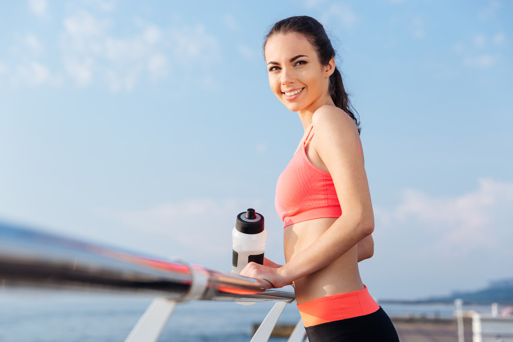 Cheerful pretty young woman athlete with bottle of water standing and smiling on pier