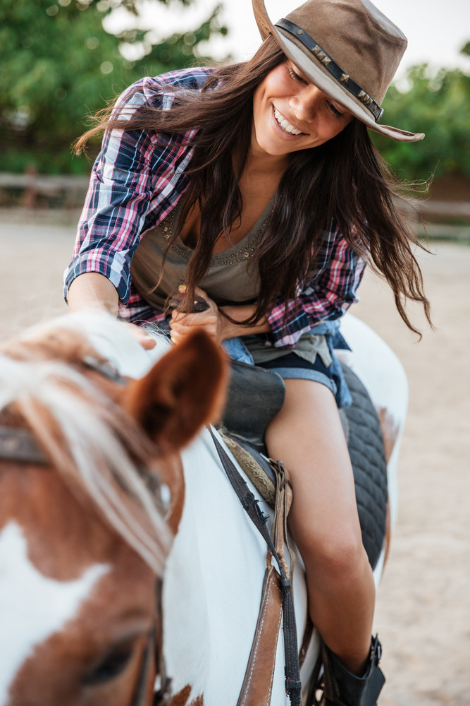 Cheerful pretty young woman cowgirl enjoying riding horse in village