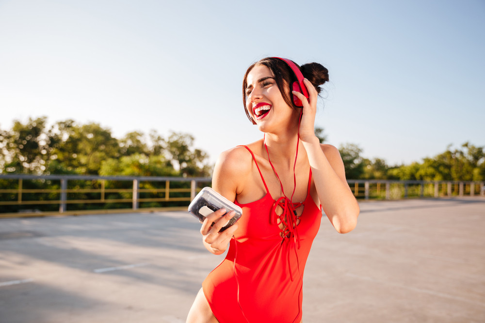 Cheerful pretty young woman in red swimsuit listening to music from retro player and laughing