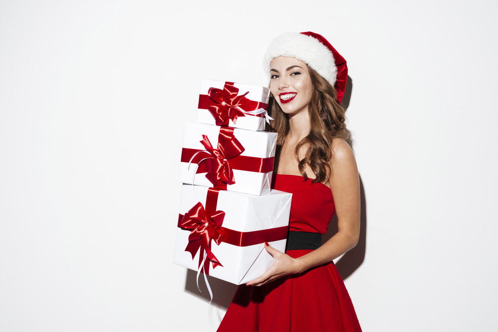 Cheerful pretty young woman in santa claus costume holding gift boxes