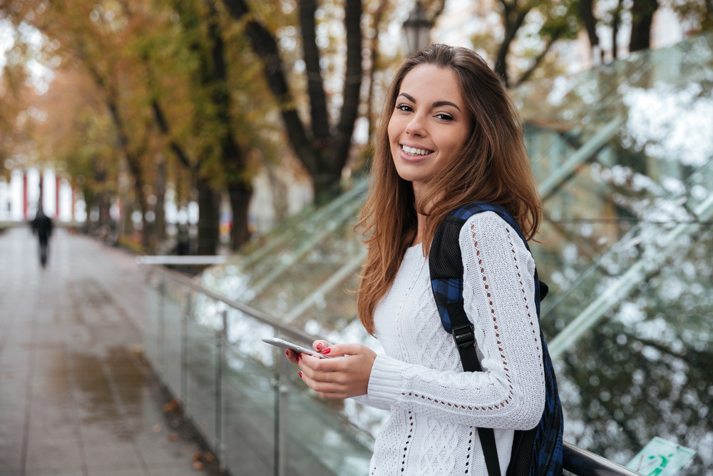 Cheerful pretty young woman with backpack using mobile phone outdoors