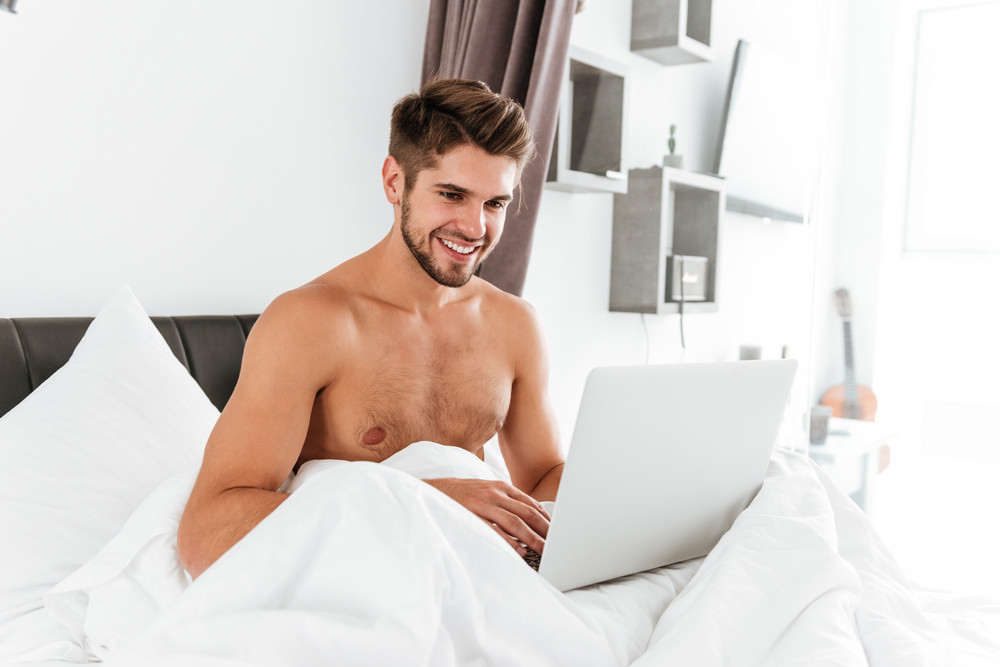 Cheerful shirtless young man sitting and using laptop in bed
