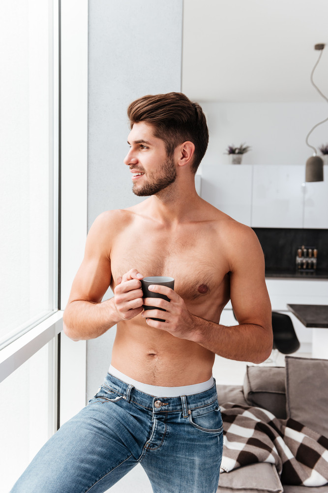 Cheerful shirtless young man standing near the window and drinking coffee on the kitchen