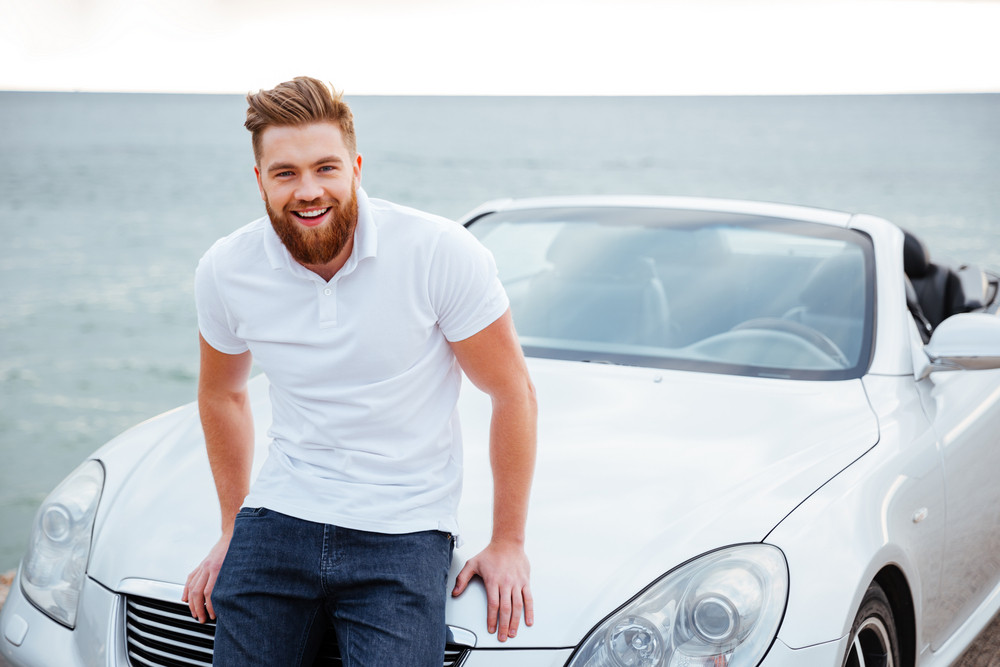 Cheerful smiling bearded man standing at his new car on beach