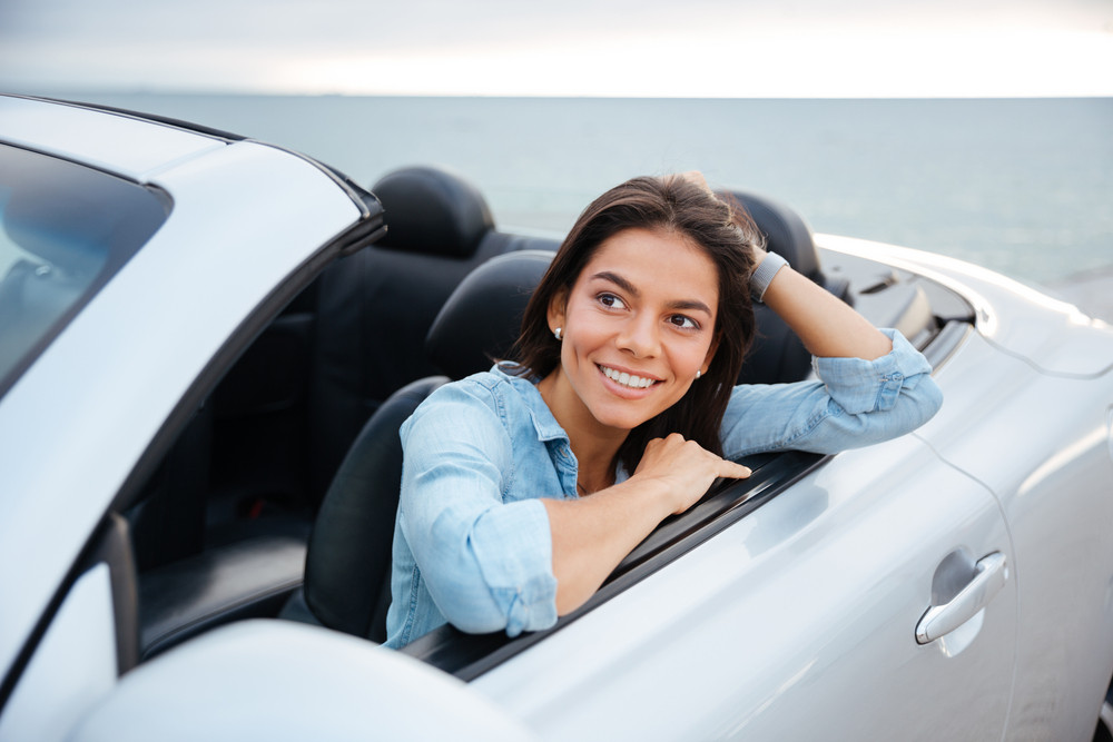 Cheerful smiling brunette woman resting inside her cabriolet parked on the beach