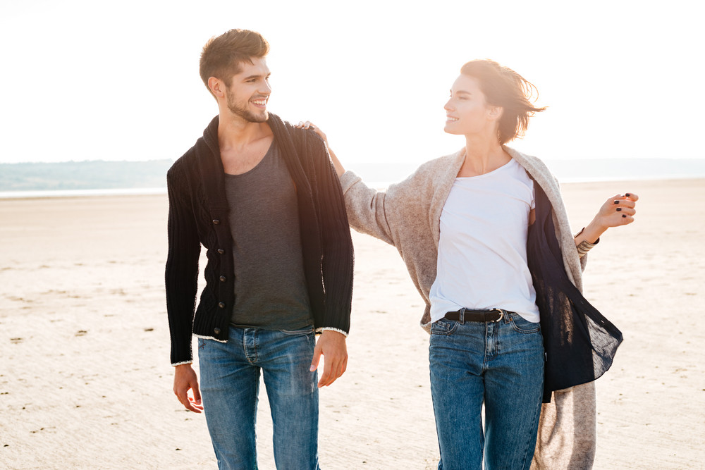 Cheerful smiling casual couple having fun at the seashore together