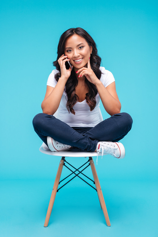 Cheerful smiling girl talking on the smartphone and sitting on the chair isolated on a blue background