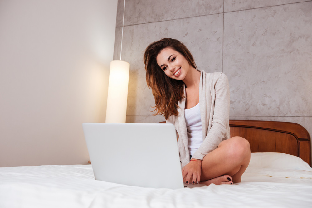 Cheerful smiling woman sitting on bed with laptop at home