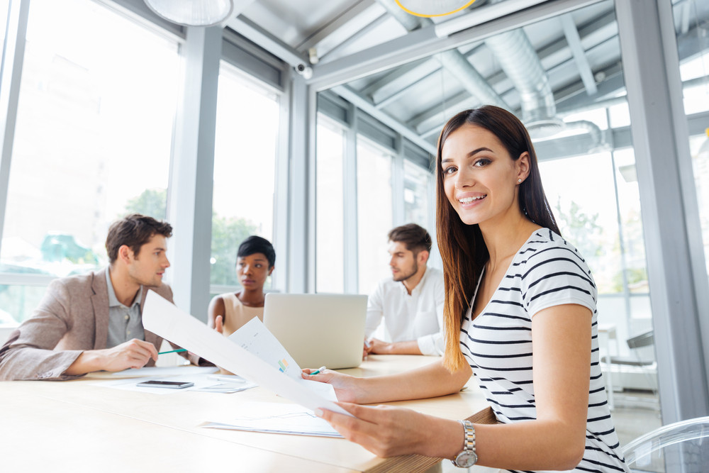 Cheerful sucessful young woman on business meeting in conference room