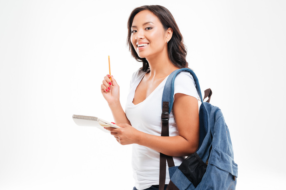 Cheerful young asian teen girl with backpack have an idea and holding notebook isolated on a white background