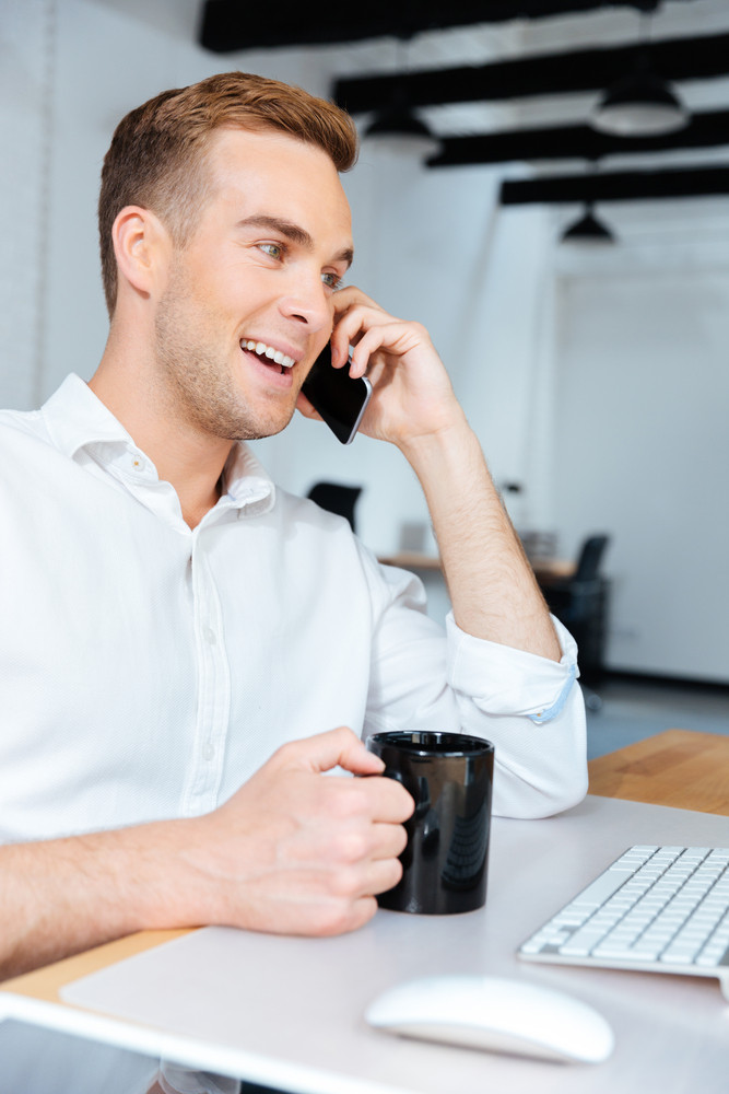 Cheerful young businessman drinking coffee and talking on mobile phone in office