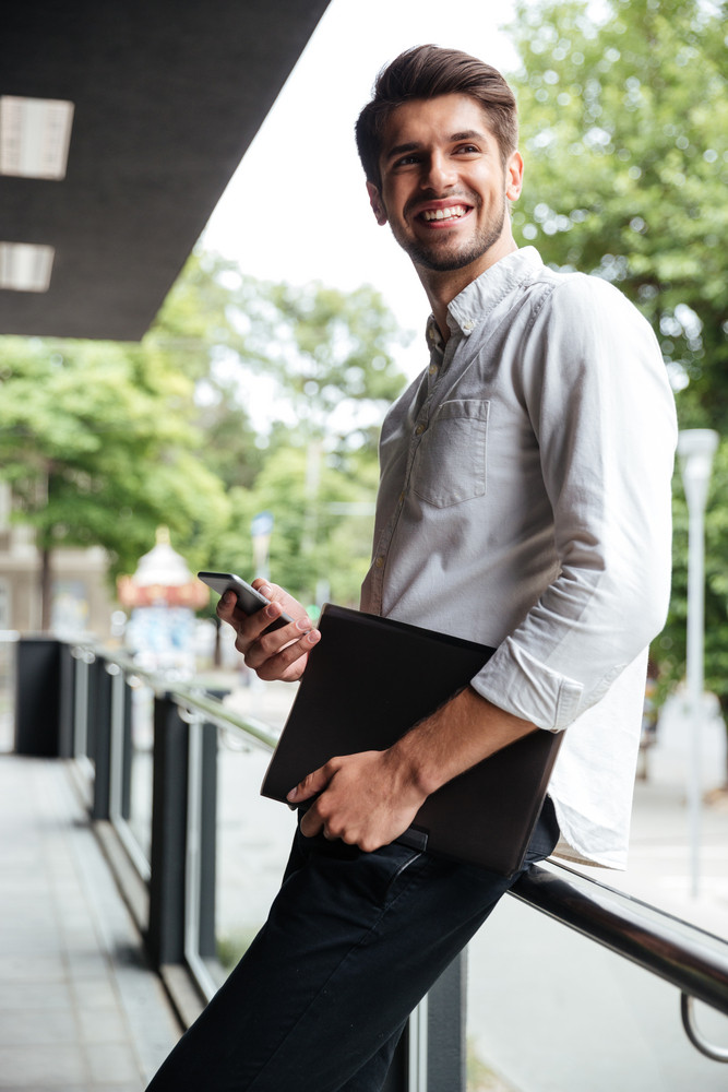 Cheerful young businessman holding folder and using mobile phone outdoors