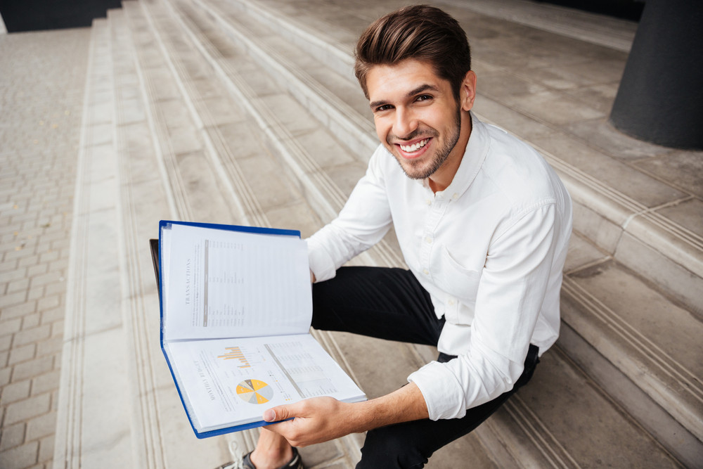 Cheerful young businessman sitting on stairs and reading business plan in folder