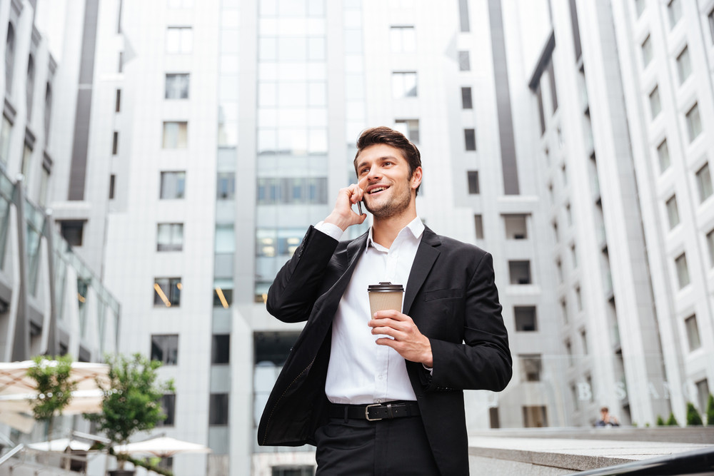 Cheerful young businessman talking on cell phone and drinking coffee in the city