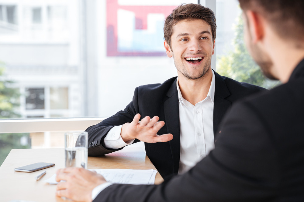 Cheerful young businessman talking with his colleague on business meeting