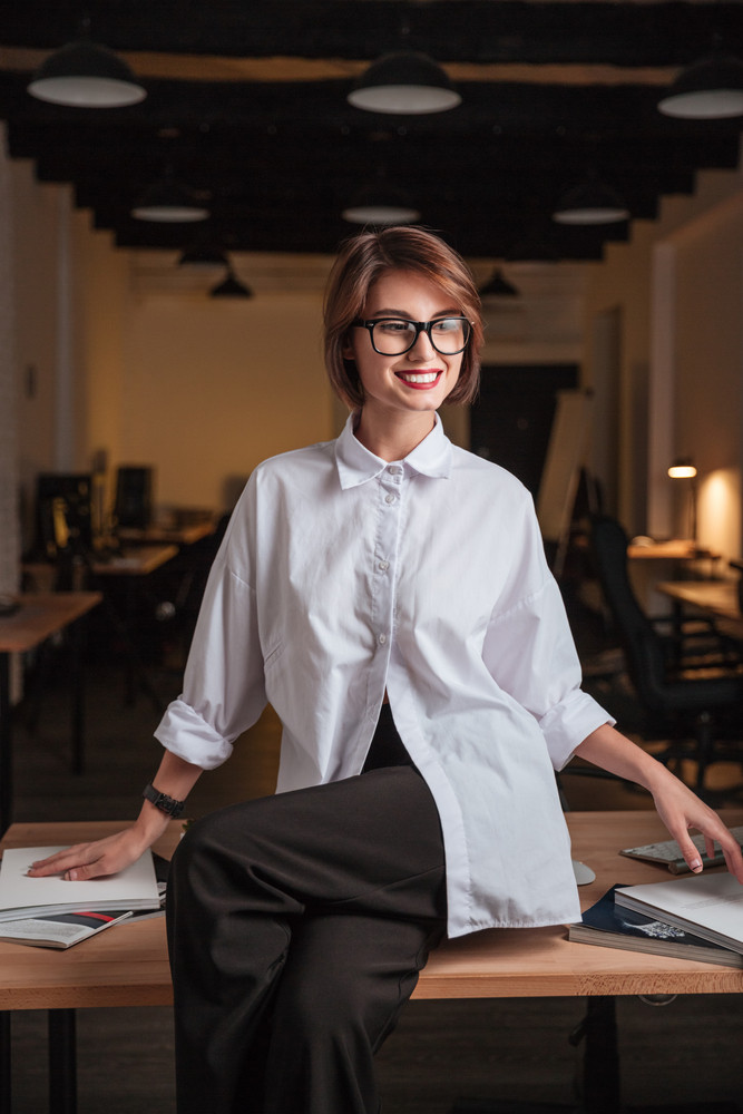 Cheerful young businesswoman in glasses