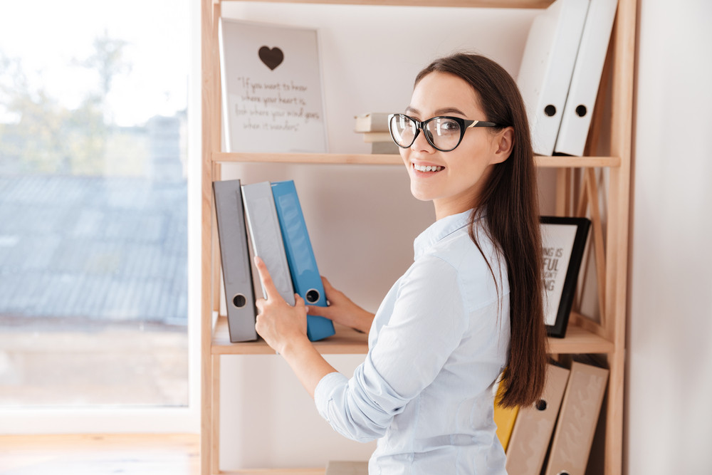 Cheerful young businesswoman taking folder from a book shelf while standing in office