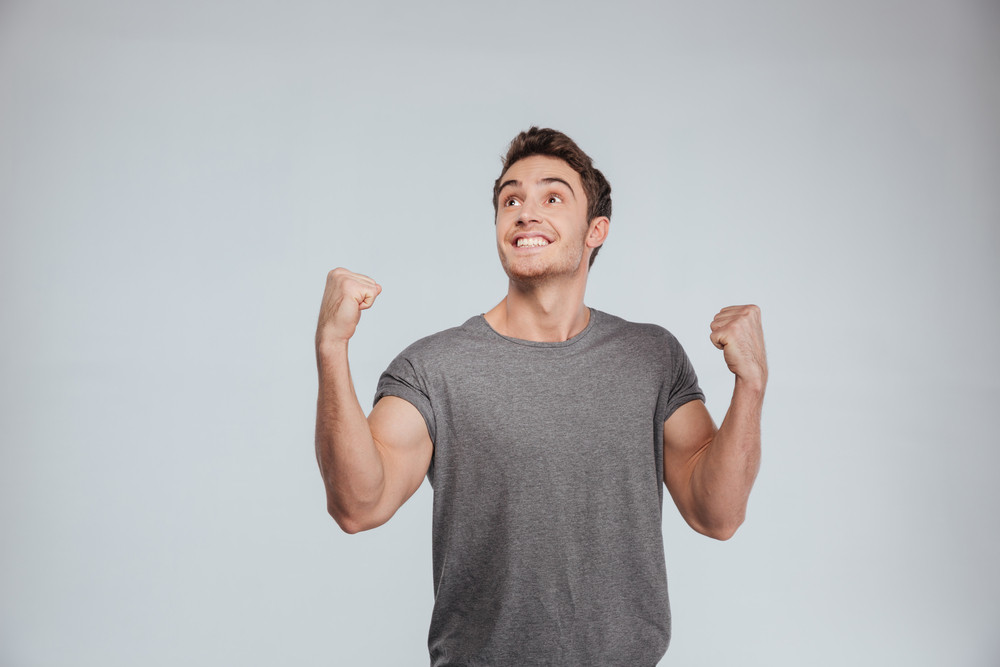 Cheerful young casual man celebrating his success over white background