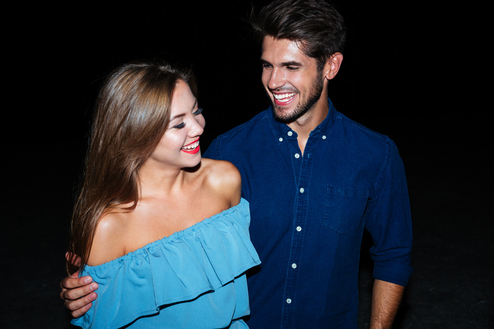 Cheerful young couple hugging and laughing together at night