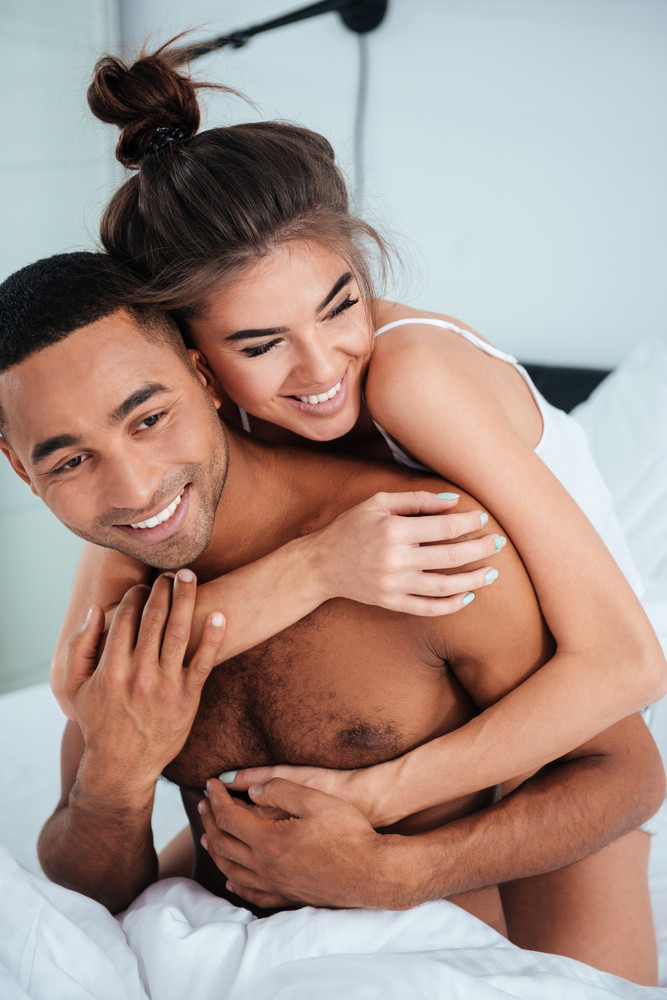 Cheerful young couple laughing and embracing on bed in the room
