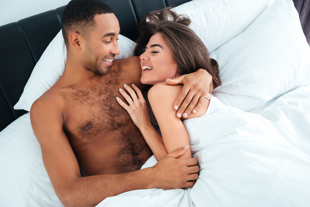 Cheerful young couple laughing and hugging in bed at home
