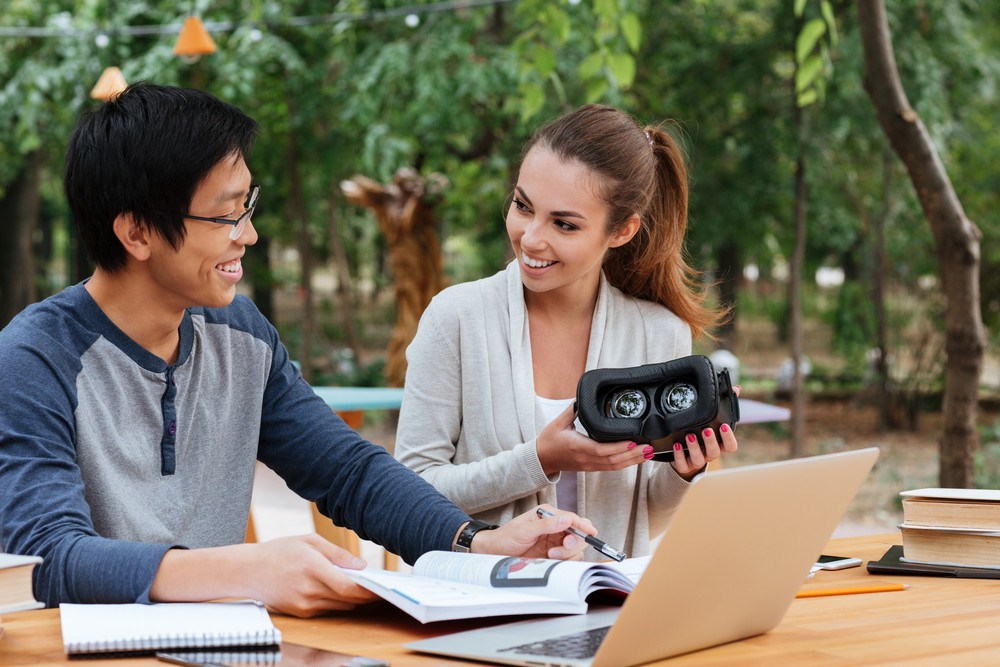 Cheerful young couple learning and holding virtual reality glasses outdoors