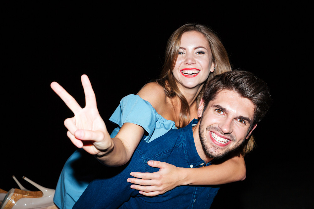 Cheerful young couple showing peace sign and having fun at night
