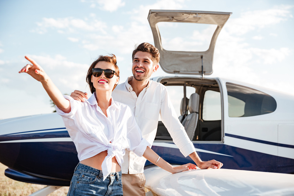 Cheerful young couple standing near small plane and pointing away