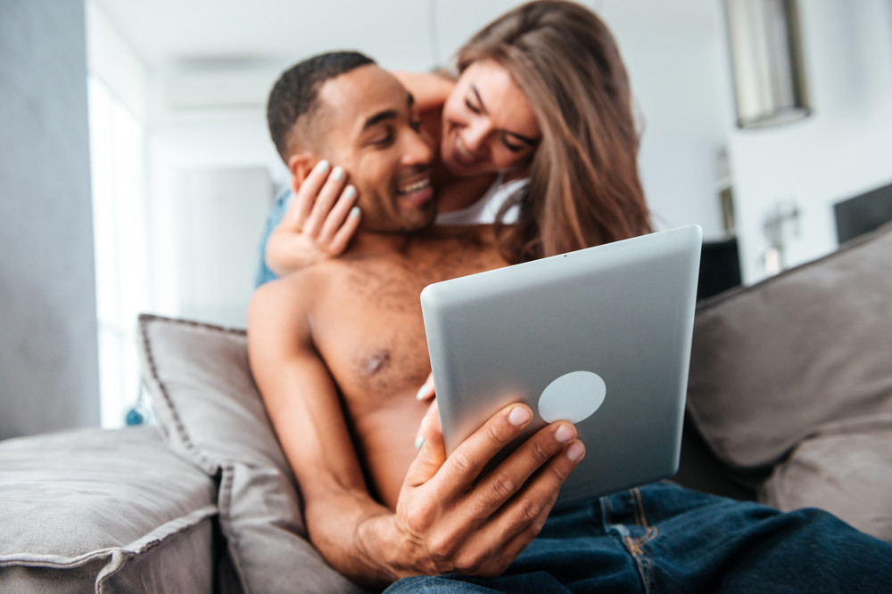 Cheerful young couple using tablet and having fun at home